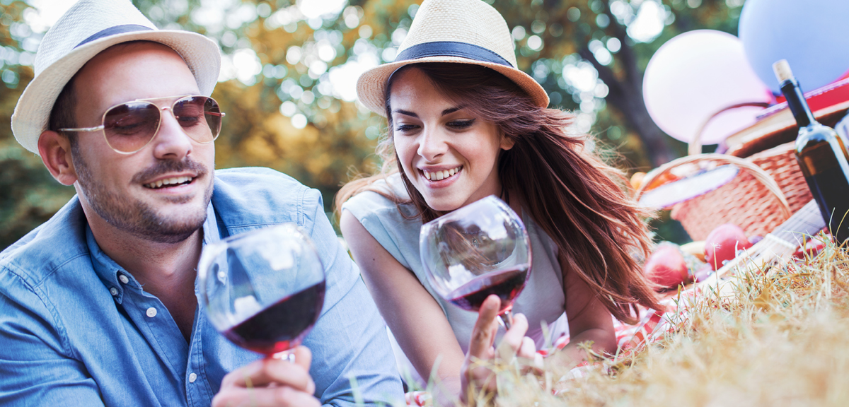 A Man and Woman Having a Picnic Happily Drinking Red Wine