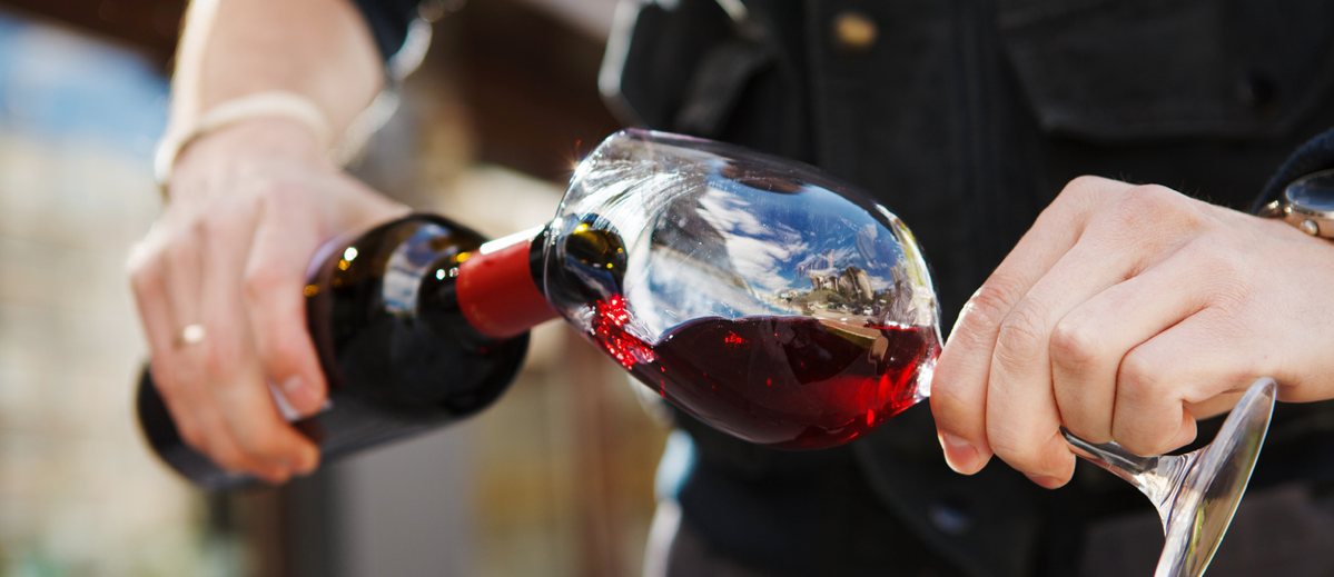 Pouring a Bottle of Red Wine into a Wine Glass
